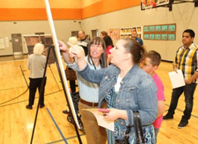 At a recent open house meeting, Transp. Proj. Manager Kristi Bachman (center, closest to the display) answers citizens' questions about a project to build a new bridge over I-44 at Rtes. N and T near Republic.