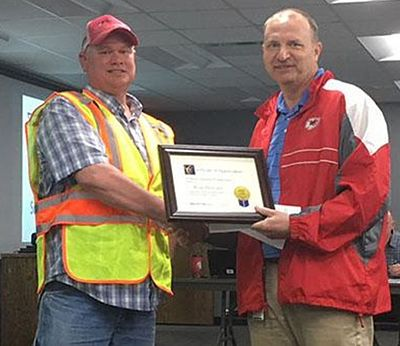 Sr. Maint. Worker Ryan Horvatic (L) is recognized by Dist. Eng. Travis Koestner with the Meritorious Safety Award for rescuing a motorist.  Ryan was treating Rte. 13 just north of the Henry/Johnson county line Feb. 22 when he saw a pickup on its top in a ditch. In the truck a woman, still in her seatbelt, hung upside down with her leg caught in the steering wheel. Removing the woman from the pickup, he determined she was not seriously hurt. Ryan got her into his truck to await the arrival of law enforcement and an ambulance.
