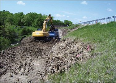 The contractor used a large track hoe to rough-in a haul road into the existing slope so that trucks could drive in and out.
