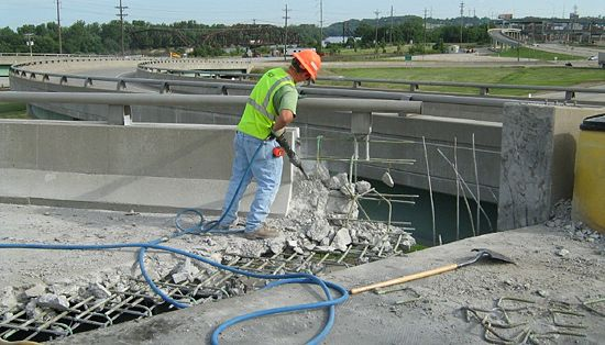 Removal of an existing expansion joint along with a portion of the concrete deck and barrier