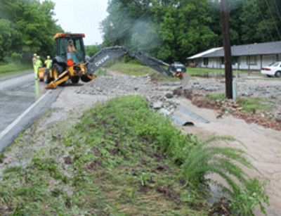 Inter. Maint. Worker Jason Bonner operates a backhoe to repair drainage pipe damage on Rte. 413 in Reeds Spring during recent flooding.