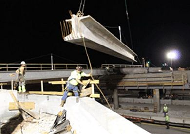Contractor crews hoist a girder into place as part of the Battlefield Road/Rte. 65 interchange reconstruction project in Springfield. When completed this fall, the project will feature a new higher, slightly wider bridge over Rte. 65 with a diverging diamond traffic pattern.