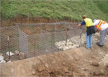 Shows the baskets in place, anchored with T-posts, and hand-placing the rock to start the filling process of the gabion baskets.
