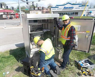 Sr. Electricians Randall Vandelicht (kneeling) and Tudor Rafa perform preventative maintenance on a signal box at the Missouri Blvd./Rte. 54 interchange in Jefferson City.