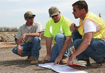 A Sr. Construction Inspector, Sr. Construction Technician and a contractor employee check plans on an interstate project.