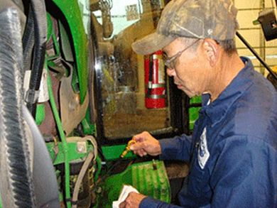 Sr. Equipment Technician Khoa Nguyen services a tractor to be used for this month's mowing.