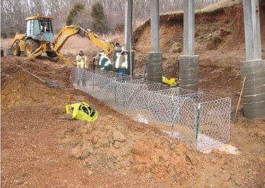 H piles are protected by concrete collars. Gabion baskets are being installed and anchored with T-posts.