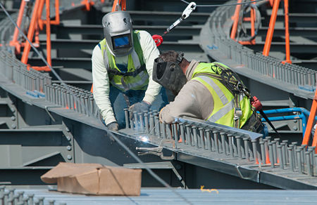 Workers weld stay-in-place corrugated steel forms in preparation for the slab pour.