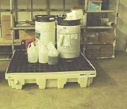 Drums properly labeled and stored on secondary containment