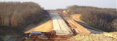 "The ""rock cap"", in place for a new highway, is the top 2 ft. of material laid before asphalt or concrete is placed on the new road. The rock cap is graded to the final elevation of the road, provides a stable base for the surface and allows water to drain from under the road without compromising the pavement or ground around the highway."