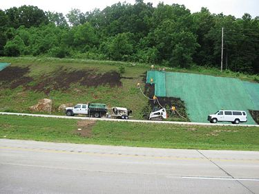 MoDOT maintenance in the former District 9 applying compost and installing a geotextile blanket on the roadside slope.