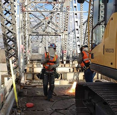 American Bridge Co. workers cut the steel deck to remove the Fairfax Bridge, the U.S. 69 bridge over the Missouri River built in 1935. The workers wear a body harness for fall protection since they are within 6 ft. of the free edge. Two blast events to demolish the bridge are tentatively scheduled for January 2015.